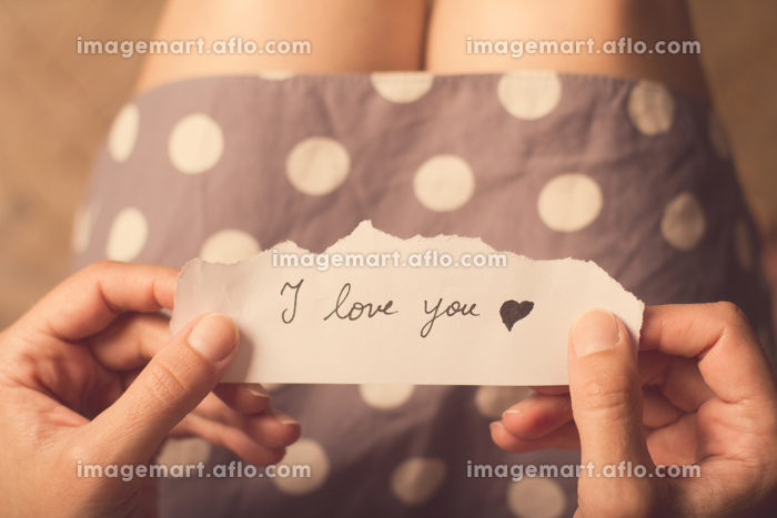Woman holding a paper note with the text I love youの販売画像