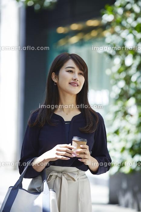 コーヒーを持って歩く日本人女性のポートレートの販売画像