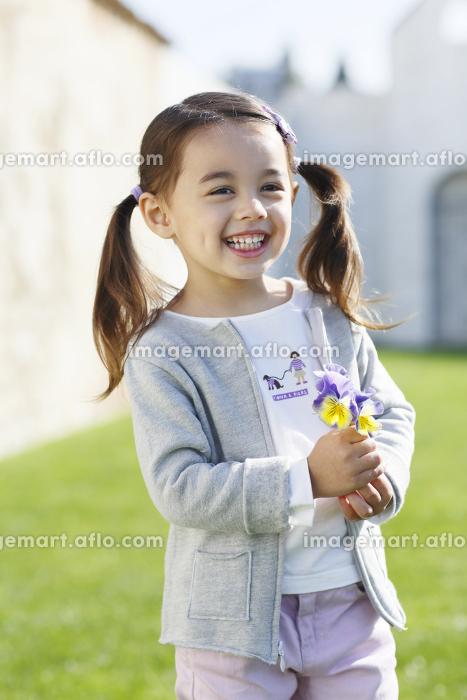 花を持って微笑む女の子の販売画像