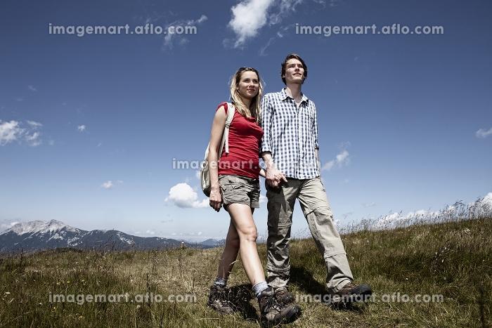 Couple walking in grassy fieldの販売画像