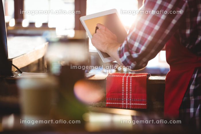 Mid section of waiter using digital tabletの販売画像