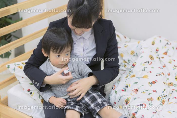 体温計で熱を測る子供