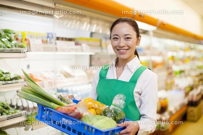 野菜の入った箱を持つ女性店員の販売画像