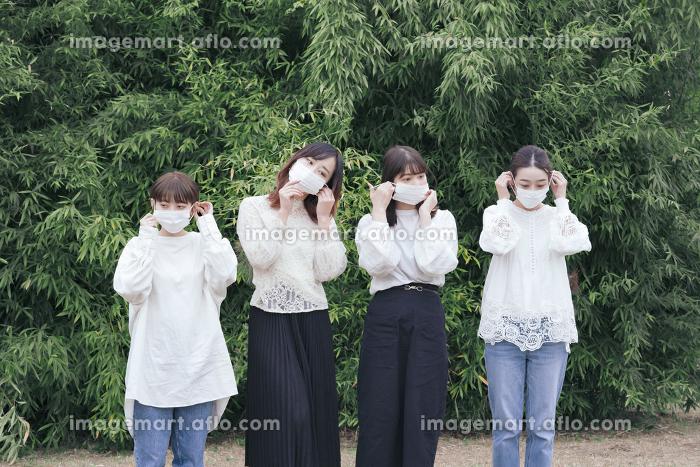 屋外でマスクを装着する日本人女性4人の販売画像