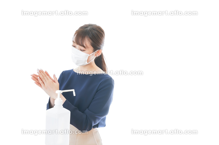 手のアルコール消毒をする若い女性の販売画像