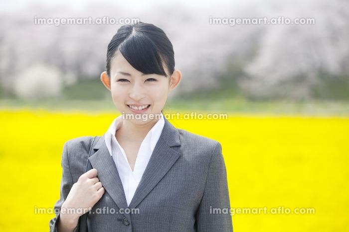菜の花畑で微笑むビジネスウーマンの販売画像