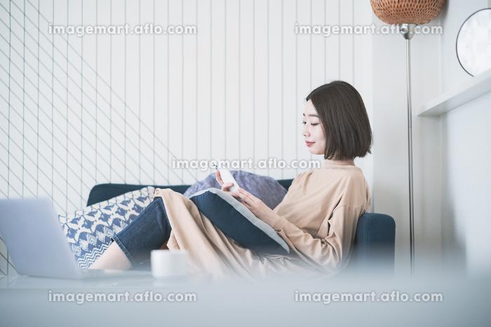 ステイホーム・ソファでリラックスする女性の販売画像