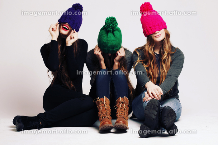Studio fashion portrait of a group of three young beautiful model posing in winter leather shoes, warm clothes and colorful knitted caps. Friends having fun. Consumer concept, winter fashionの販売画像