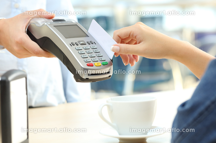 Waiter charging with credit card reader in a bar