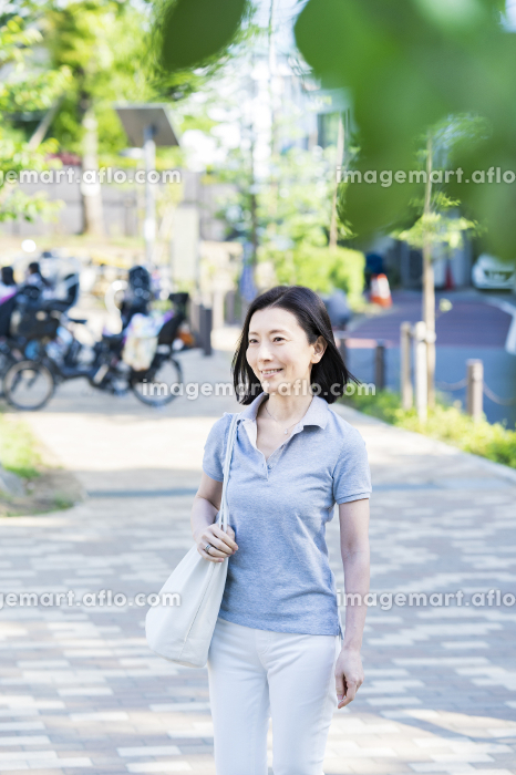 リラックスした表情で散歩する中年女性の販売画像