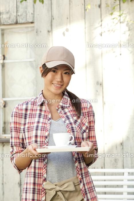 コーヒーを運ぶカフェ店員