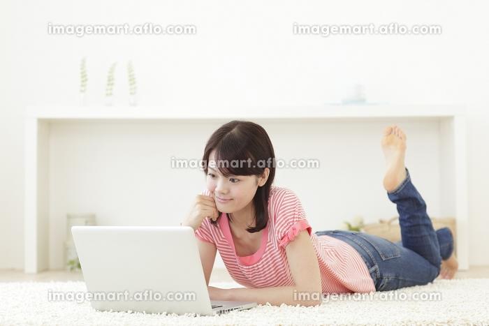 リビングで寝そべりパソコンをする若い女性の販売画像