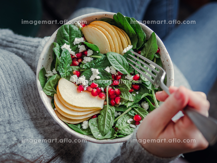 Girl holding salad with spinach, pear, pomegranate, cheeseの販売画像