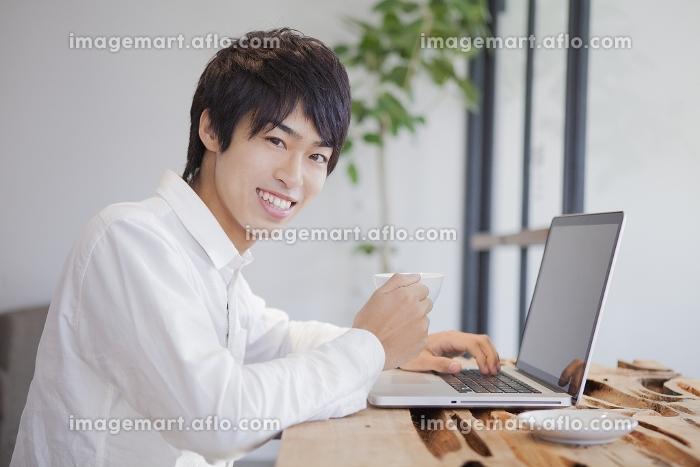 カフェでパソコンをしている男性の販売画像