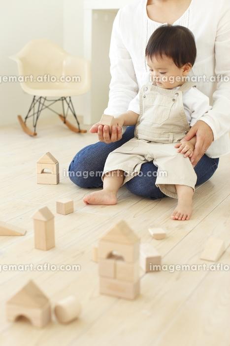 フローリングのリビングでお母さんと積木で遊ぶ赤ちゃん