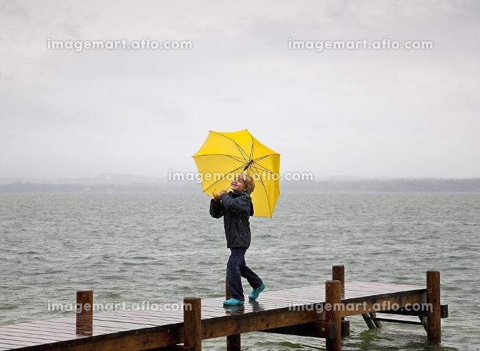 Boy carrying umbrella on wooden dockの販売画像