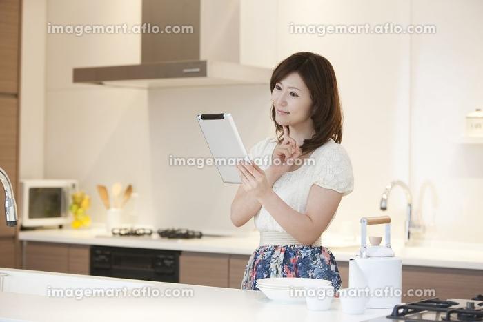 タブレット型コンピューターでレシピを調べる女性の販売画像