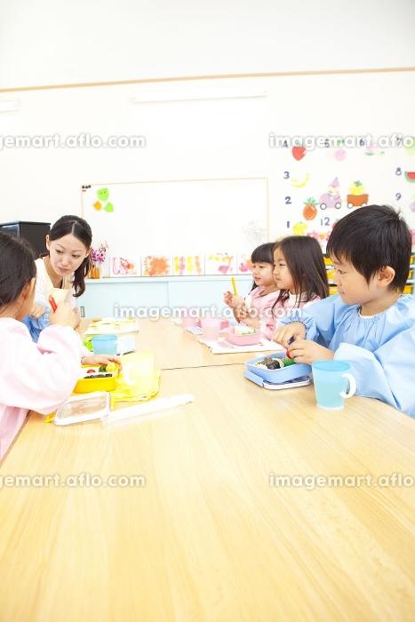 お弁当を食べる幼稚園教諭と幼稚園児の販売画像