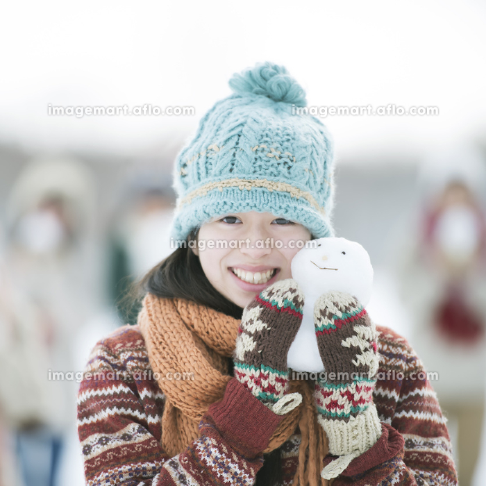 雪だるまを持ち微笑む中学生の販売画像