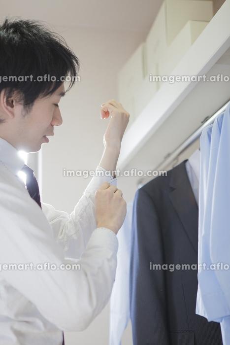 シャツのボタンを留める男性の販売画像