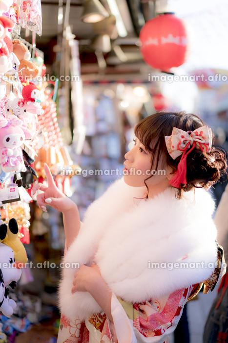 参道でお土産を物色する振袖の女性