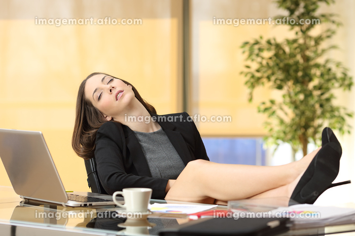Lazy or tired businesswoman sleeping at workの販売画像