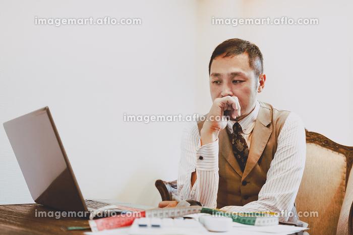 ノートパソコンの前で考え事をする男性の販売画像