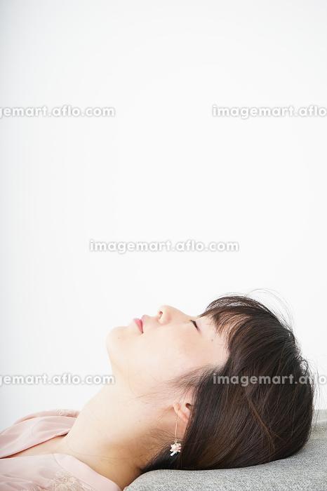 体調不良で横たわる若い女性の販売画像