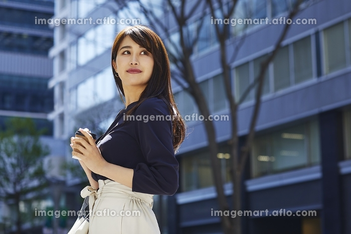 コーヒーを持って歩く日本人女性のポートレート