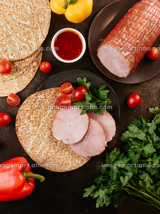 fresh homemade sausage on a dark background with vegetablesの販売画像