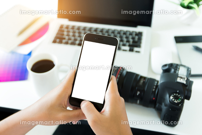 creative photogeapher holding phone white screen on workspace table, phone blank screen for adjustment mobile appの販売画像