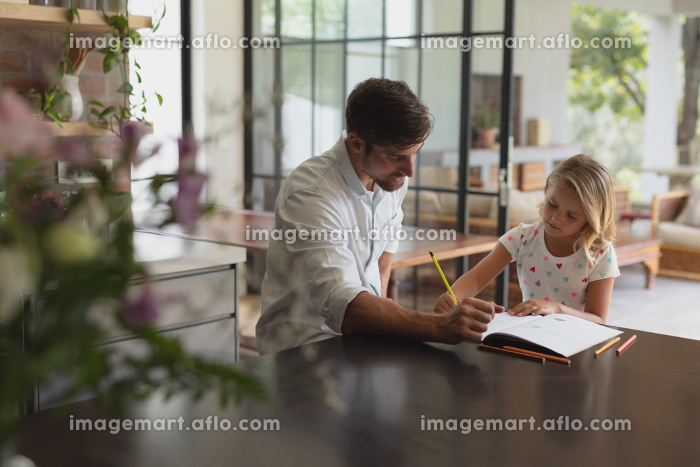 Front view of Caucasian father helping his daughter with homework in a comfortable homeの販売画像