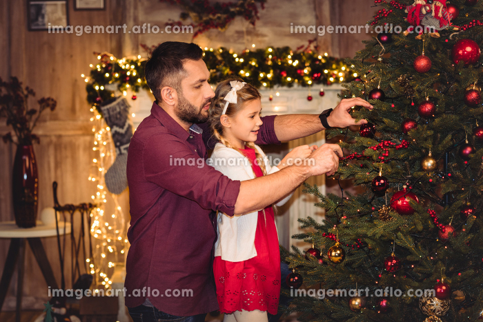 Father and daughter decorating christmas treeの販売画像