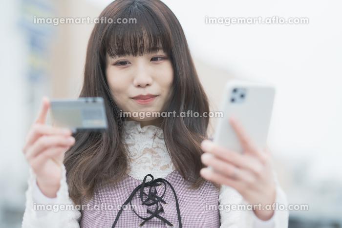 クレジットカードとスマートフォンでネットショッピングをする女性の販売画像