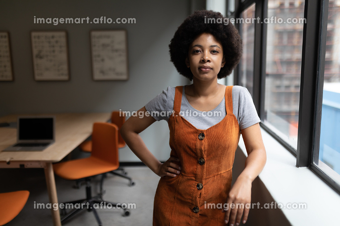 Mixed race businesswoman working in creative office. portrait of a woman looking at camera. social distancing in workplace during covid 19 pandemic.の販売画像