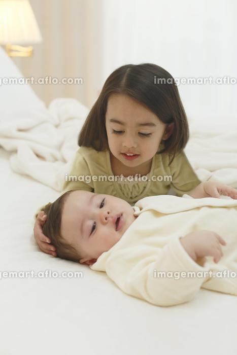 寝室で不機嫌な赤ちゃんをあやす女の子の販売画像