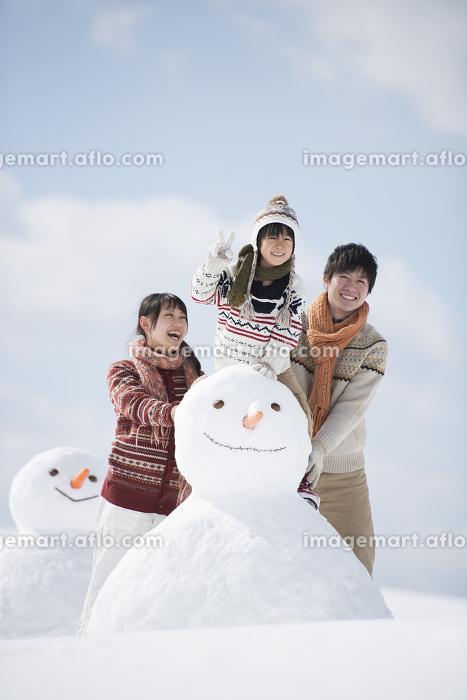 雪だるまの側で微笑む家族の販売画像