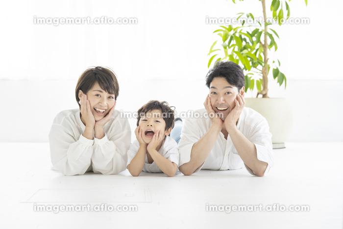 寝そべって同じポーズを取る親子3人の販売画像