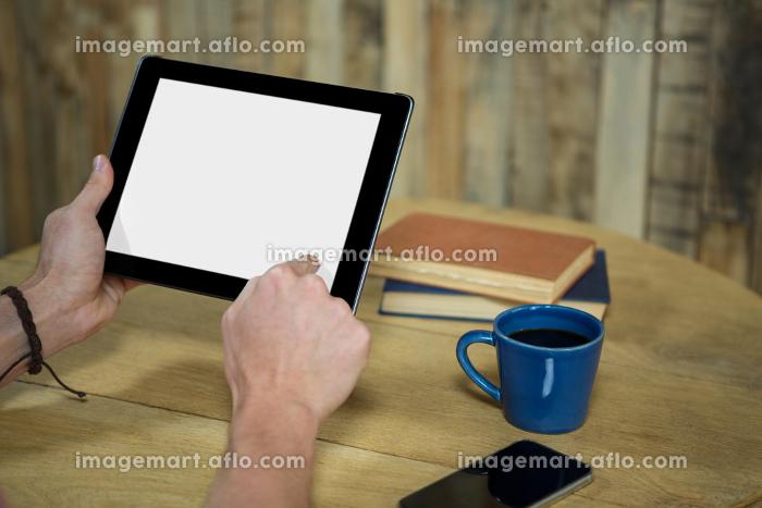 Man using digital tablet in coffee shop
