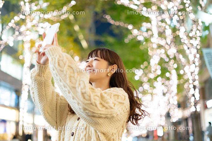 イルミネーションを撮影する若い女性