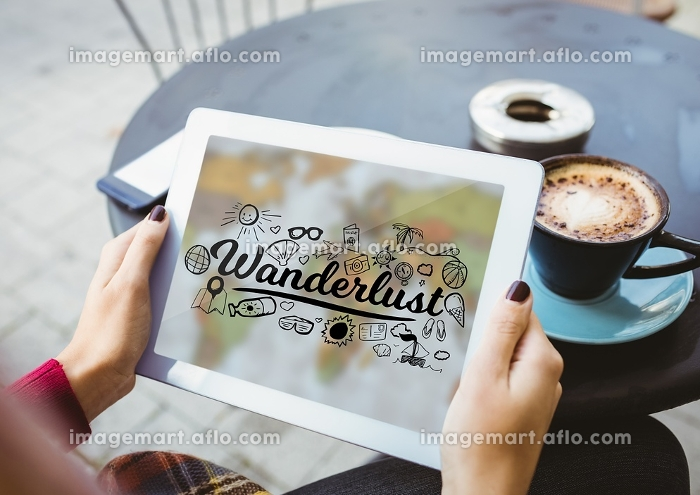 Woman at cafe holding tablet showing black wanderlust doodles against blurry mapの販売画像