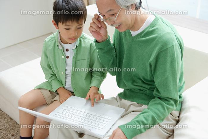 パソコンを操作する祖父と孫の販売画像