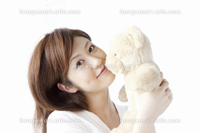 ぬいぐるみとキスをする女性の販売画像