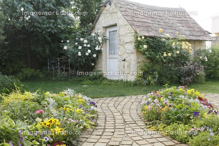 花と緑の溢れる庭と小さな小屋