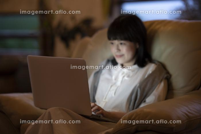 ひかえめな照明の部屋のソファで、ノートパソコンを使う若い女性の販売画像