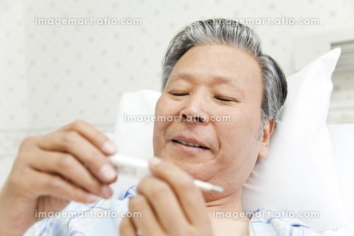 体温計を見て微笑む患者