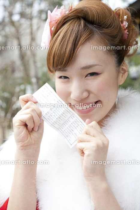 おみくじの結果を見せ微笑む振袖姿の女性の販売画像