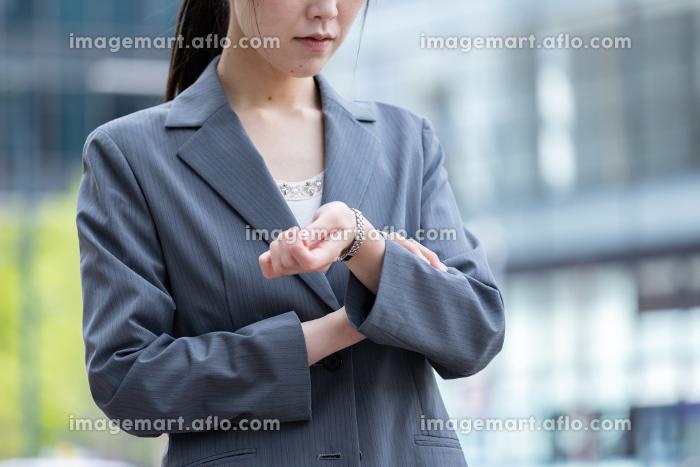 オフィス街で腕時計で時間を確認する若いビジネスウーマンの販売画像