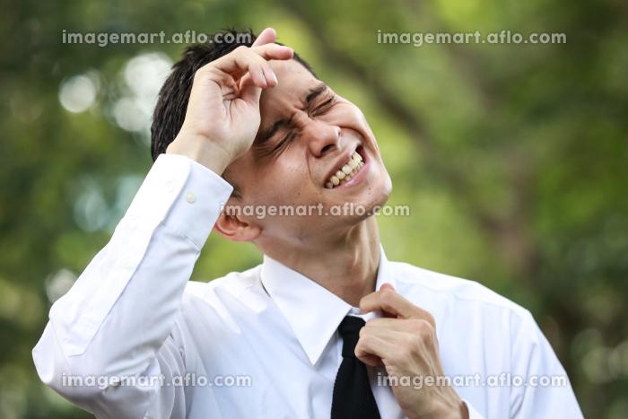 手で汗を拭う男性社員の販売画像