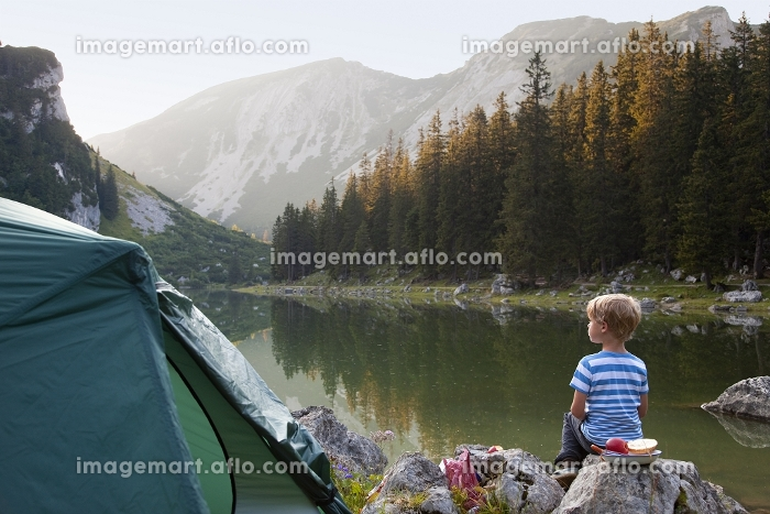 Boy relaxing at campsiteの販売画像